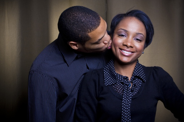 A happy african american female is being kissed on the cheek by her lover